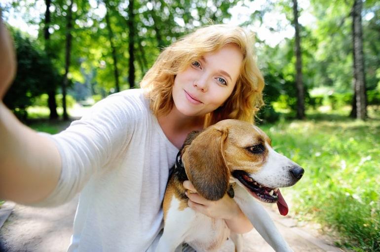Frau macht Selfie mit einem Beagle im Hintergrund Wald und Wiese. Die Haarfarbe der Frau ist ähnlich der Fellfarbe des Hundes