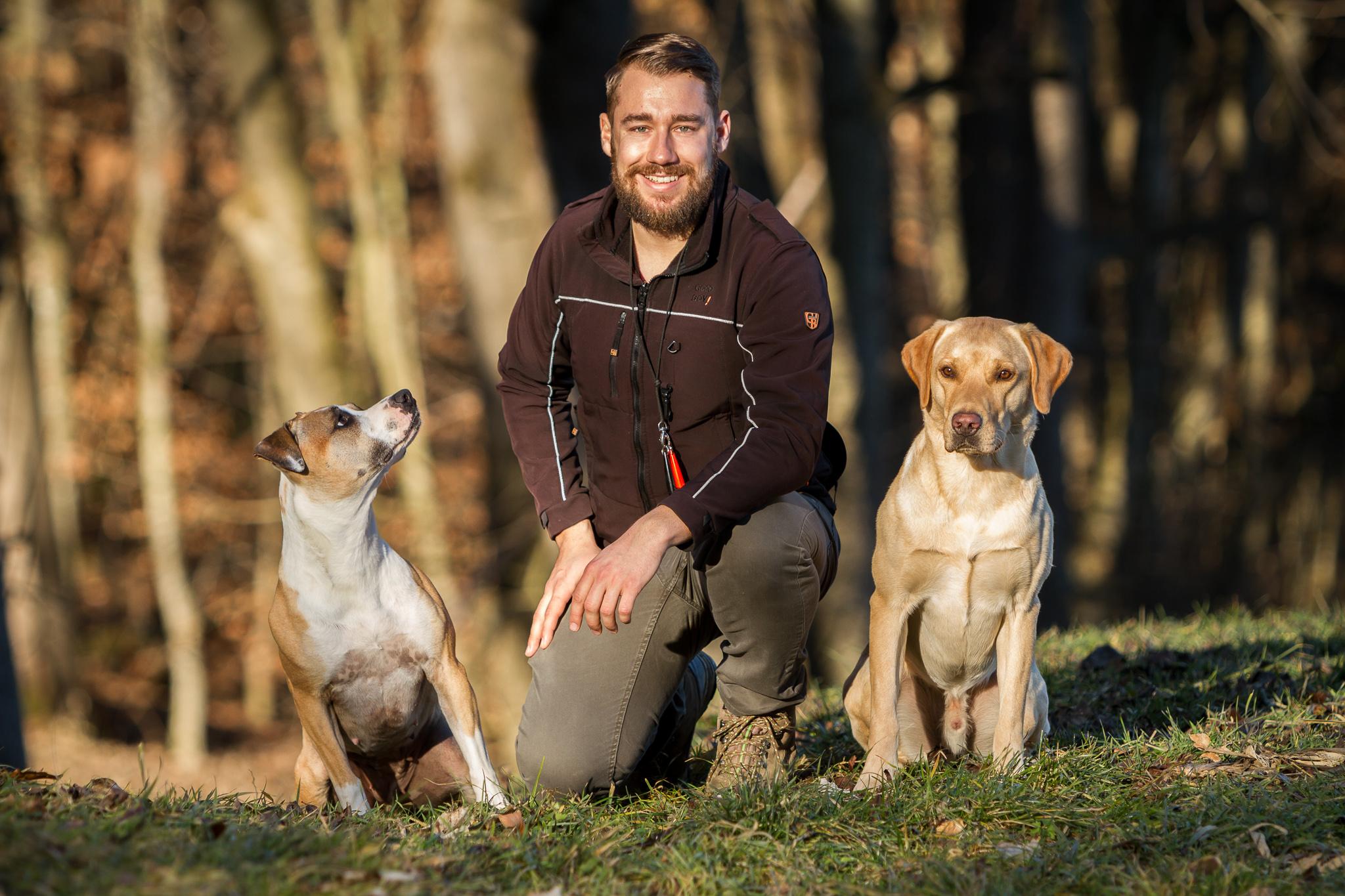 Hundetrainer Andreas Gomsi in der Hocke mit zwei Hunden neben ihm sitzend dahinter ein Wald
